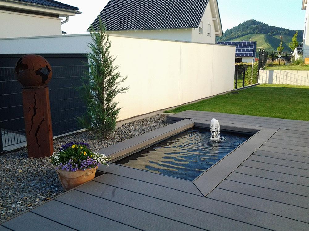 WPC-Terrasse mit eingefasstem Teichbecken und Fontäne Wasserspiel