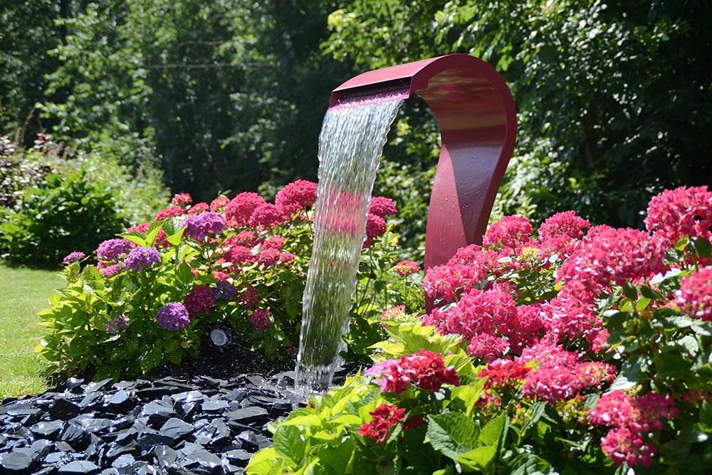 Garten-Wasserfall rosa Gartenbrunnen modern mit dunkelgrauen Steinen Brunnen in Garten integrieren