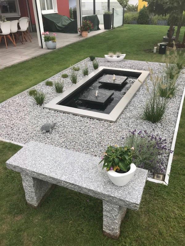 Architektonisches Wasserbecken mit Edelstahl-Umrandung und Wasserspielen in ein Kiesbett eingefasst