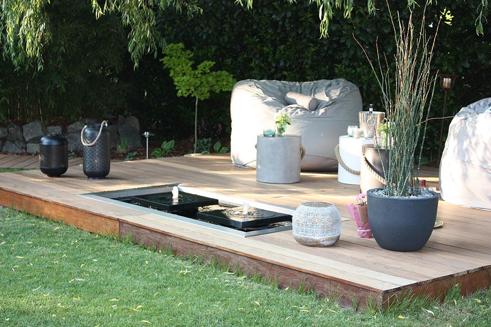 Designer-Gartenbrunnen mit zwei Quellplatten und architektonischem Langform-Wasserbecken auf Holzterrasse